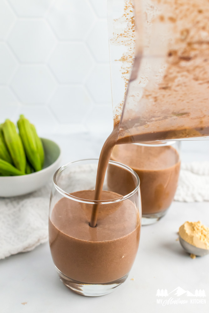 blender pitcher pouring chocolate peanut butter milkshake into glass