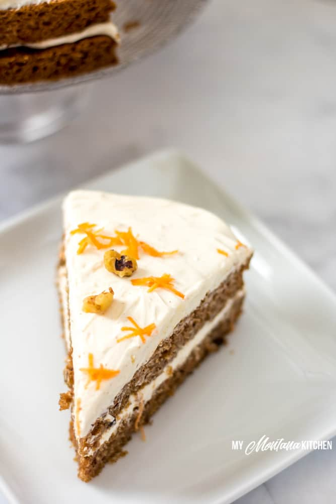 low-carb-carrot-cake-on-white-plate-with-shredded-carrots-and-walnuts
