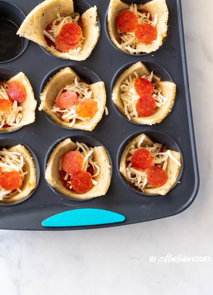 low carb pizza cups in muffin tin with mozzarella and pepperoni