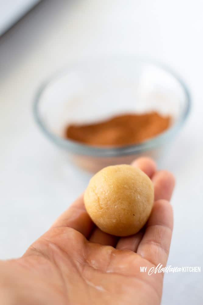 ball of snickerdoodle dough in outstretched hand