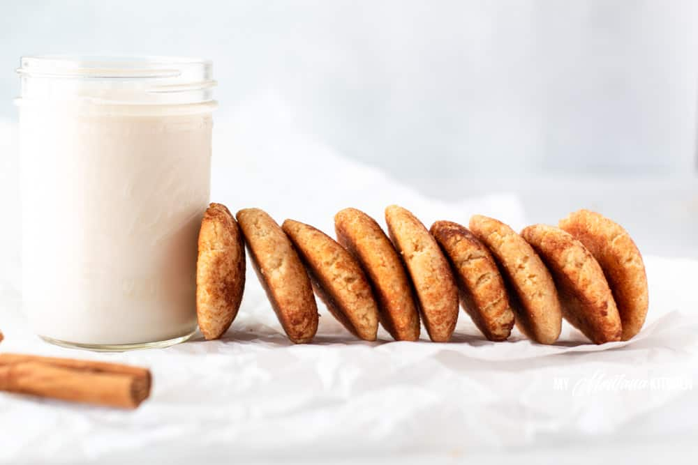 row of snickerdoodles leaning against glass of milk