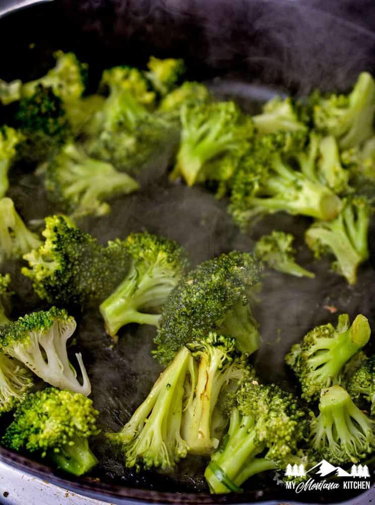 steaming broccoli in iron skillet