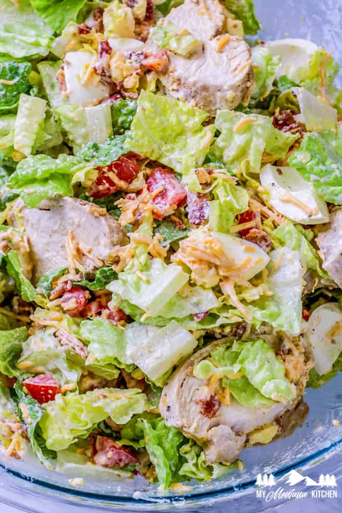 chicken cobb salad with dressing in glass bowl