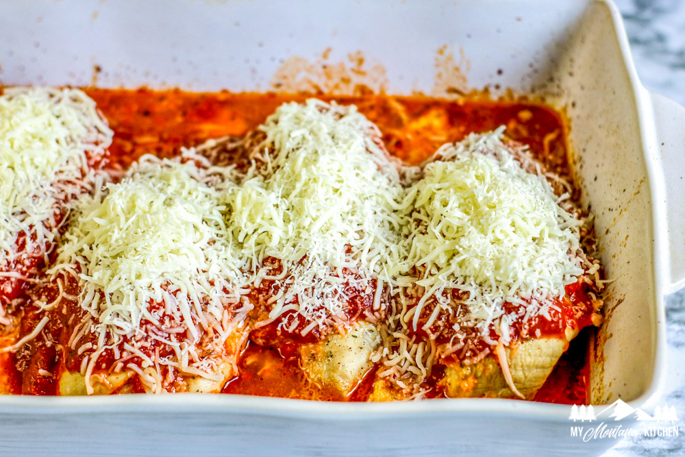 baked chicken breast with red sauce and cheese in baking pan