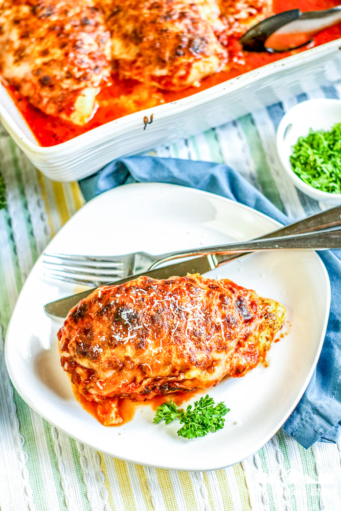 baked lasagna chicken on white plate with fork