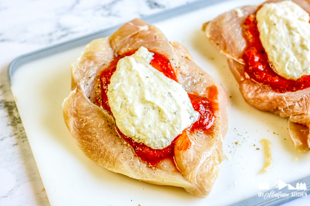 raw chicken breast with red sauce and ricotta