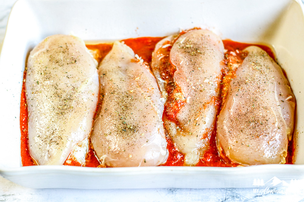 four raw stuffed chicken breasts in baking pan with red sauce