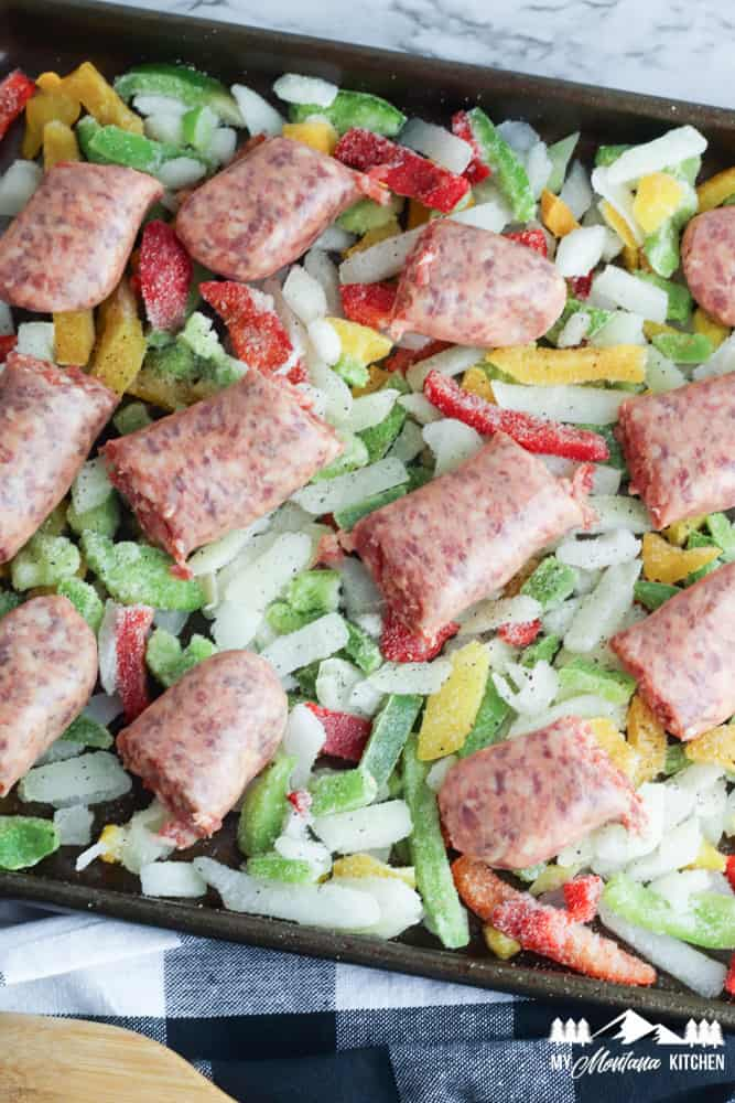 uncooked sausage and frozen peppers on baking sheet