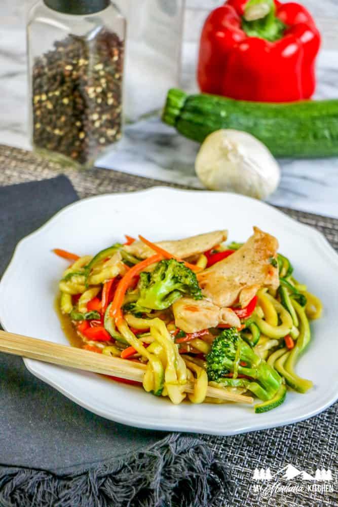healthy chicken lo mein in white dish with chopsticks